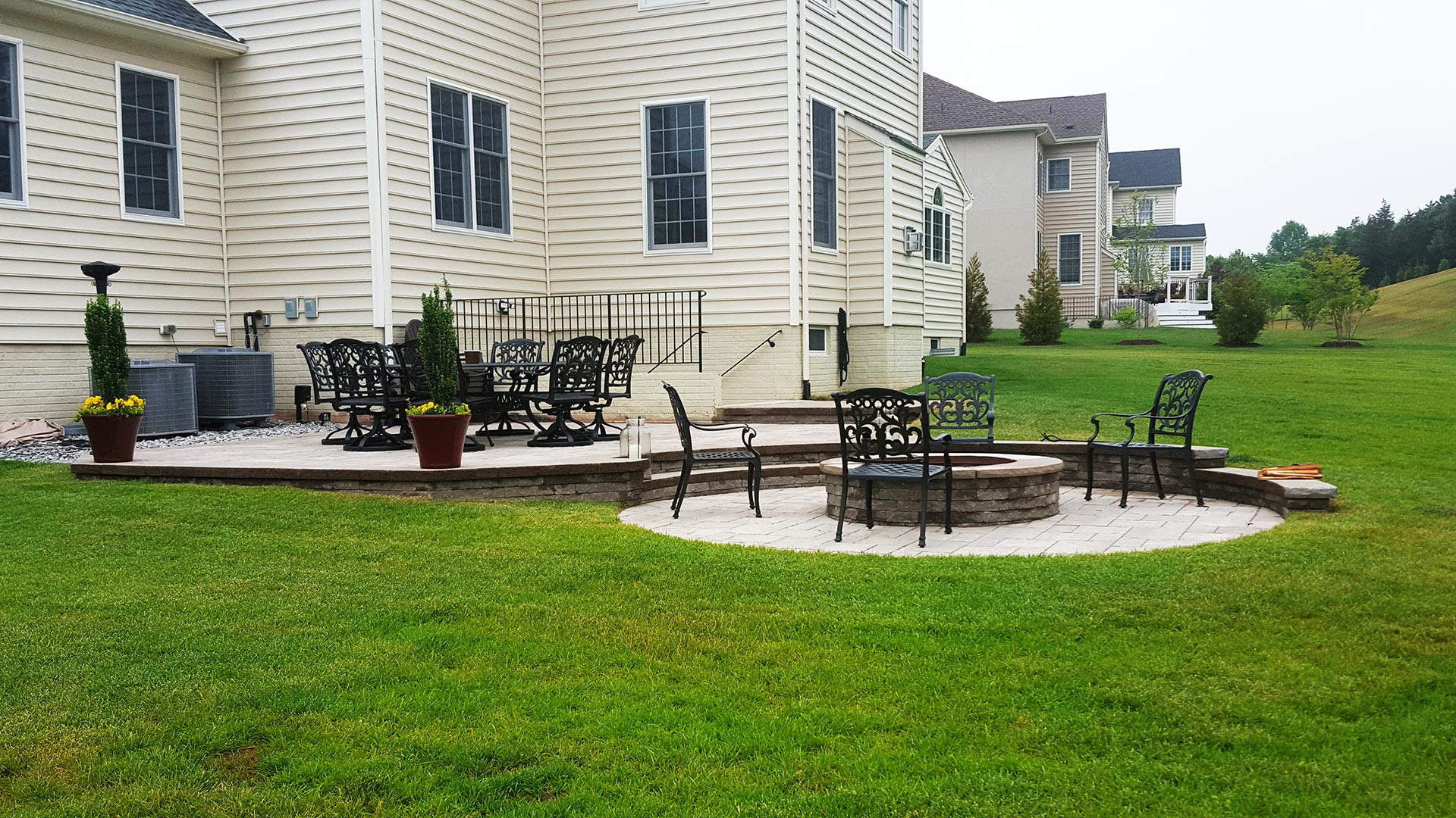 New Baltimore, VA home property with healthy lawn and custom patio and fire pit construction.