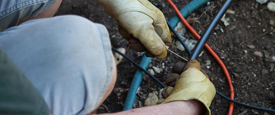 Technician adjusting an irrigation system in Bristow, VA.