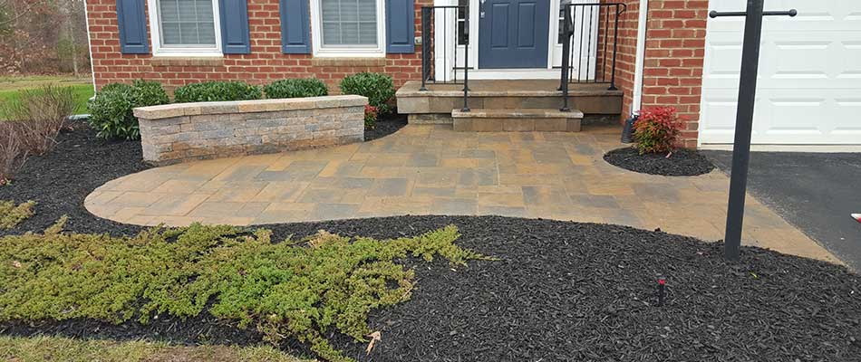 Custom patio, seating wall, and landscape installation for a Manassas, VA home.